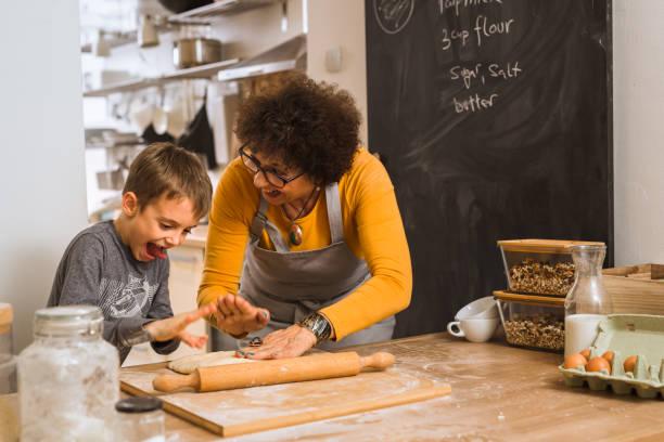 haute femme cuisson ensemble dans la cuisine avec ses petits-enfants - Photo