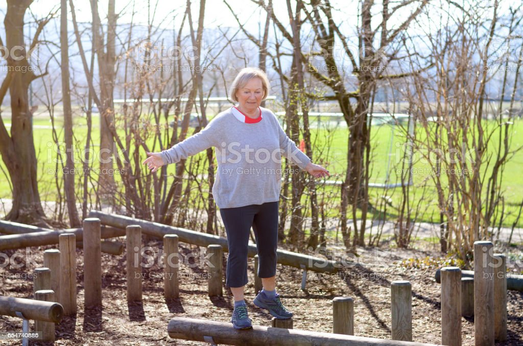 Senior woman balancing in park stock photo