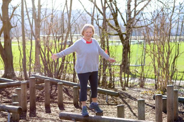 Senior woman balancing in park stock photo