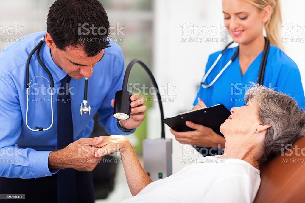 A senior woman being examined by a dermatologist stock photo