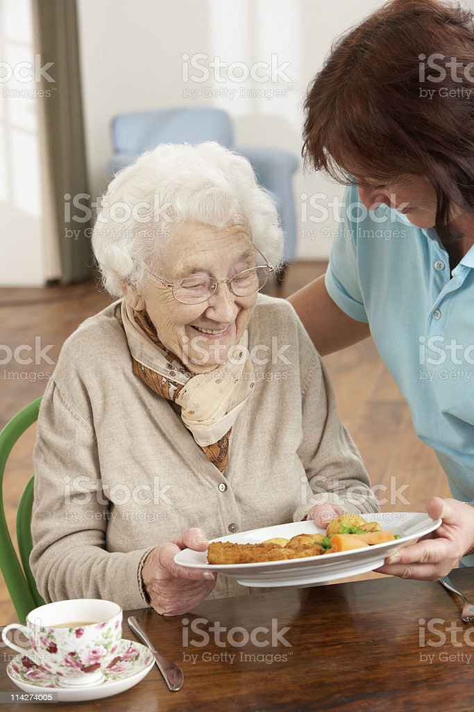Senior Woman Being Served Meal By Carer stock photo