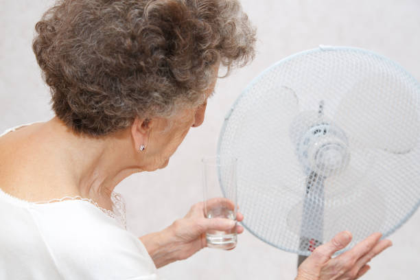 Senior woman between 70 and 80 years old stays close to the ventilator. stock photo