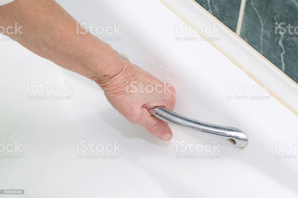 Senior woman between 70 and 80 years old wants to take a bath. stock photo