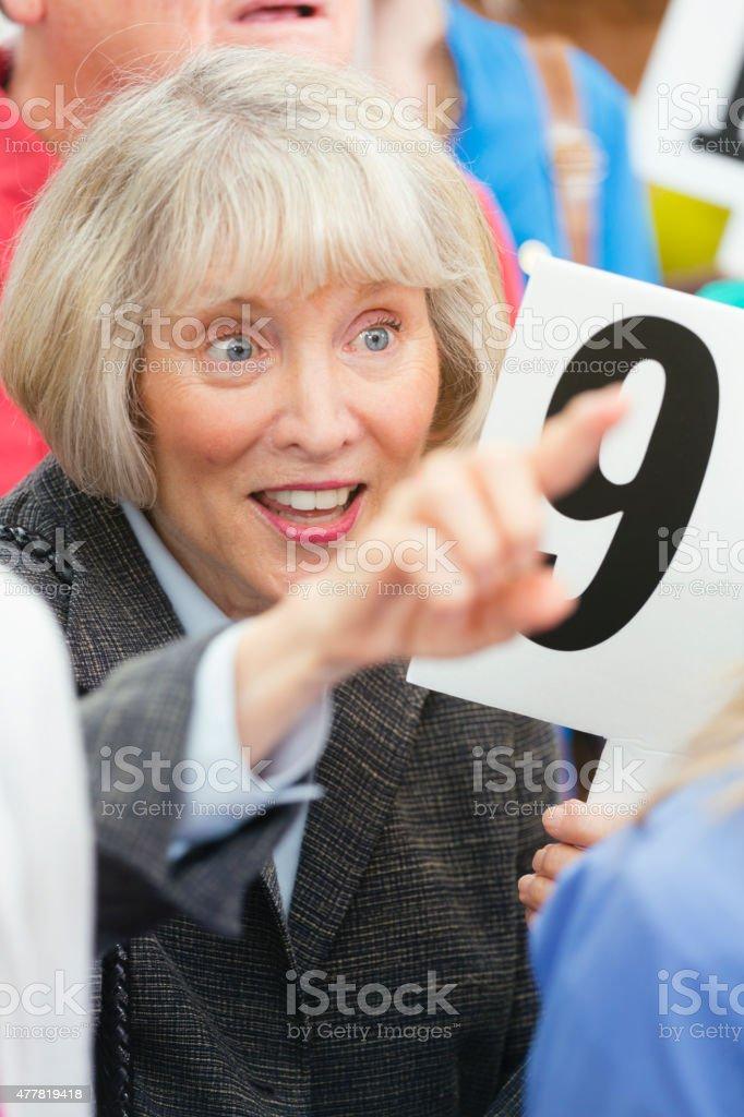 Senior Woman Bidding at a Live Auction stock photo