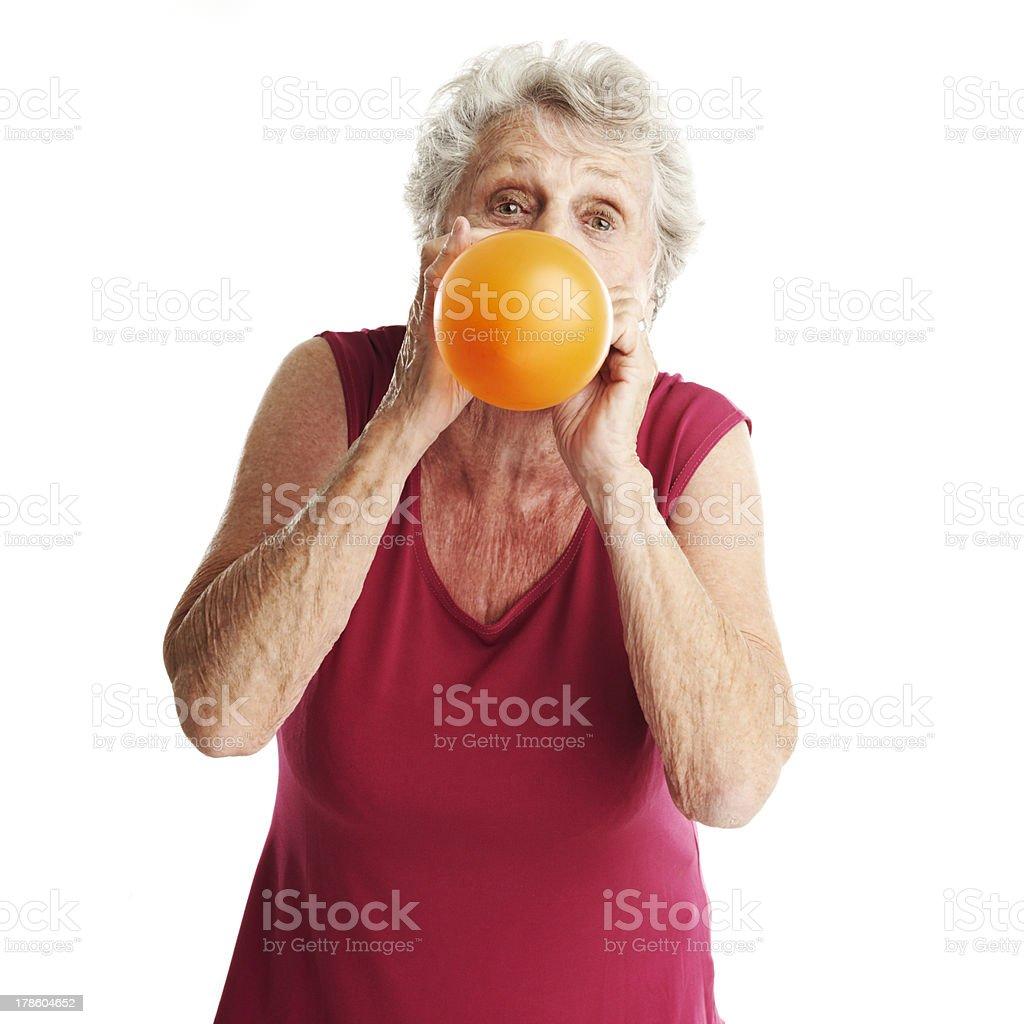 senior woman blowing balloon stock photo
