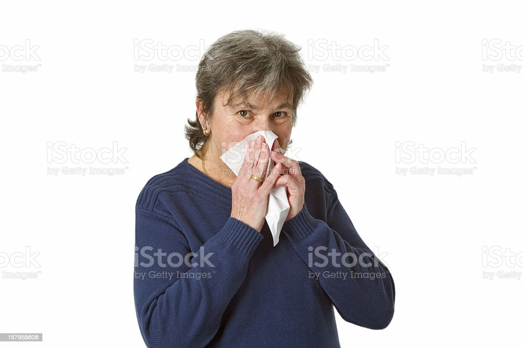 Senior woman blowing her nose stock photo