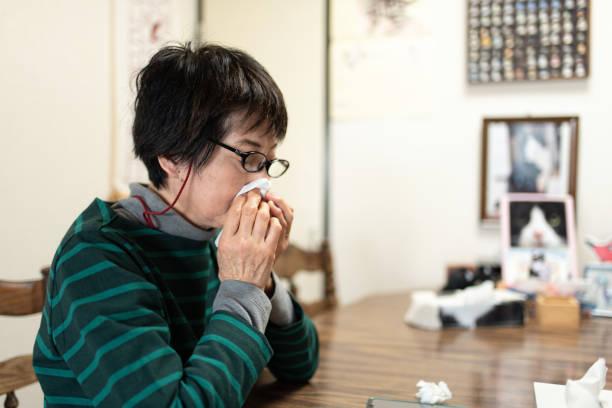 鼻を吹くシニア女性 - くしゃみ 日本人 ストックフォトと画像