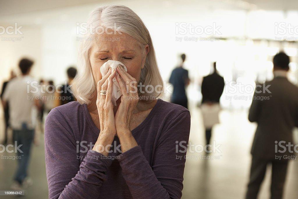 Senior woman blowing nose stock photo
