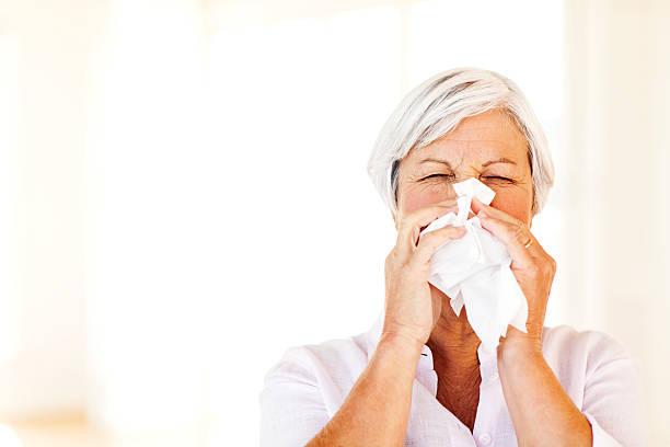 Senior Frau Blasen Nase mit Gewebe wie zu Hause fühlen. – Foto