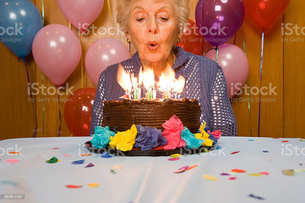 Senior woman blowing out candles on cake stock photo