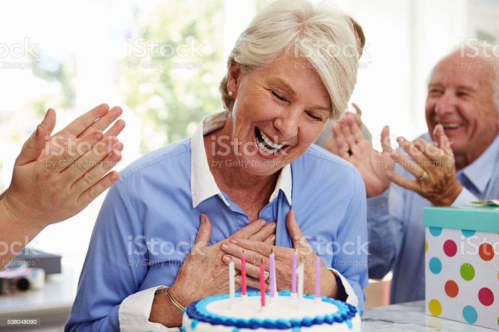 Senior Woman Blows Out Birthday Cake Candles At Family Party stock photo