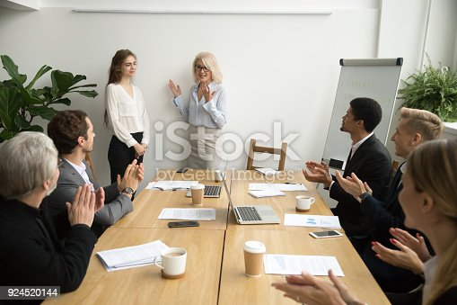 istock Senior woman boss introducing new worker, team welcoming at meeting 924520144
