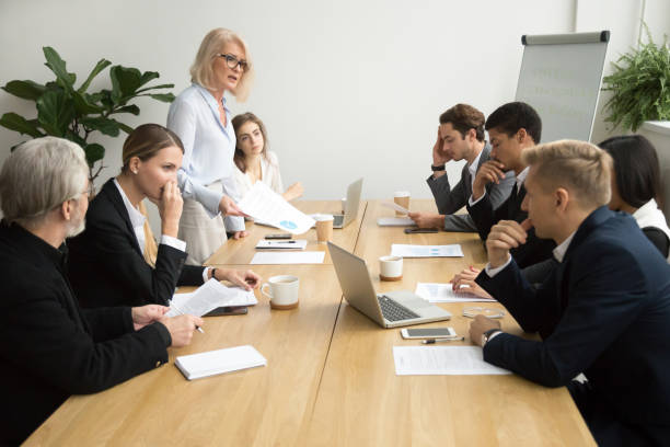 Senior woman boss scolding employees for bad work at meeting stock photo