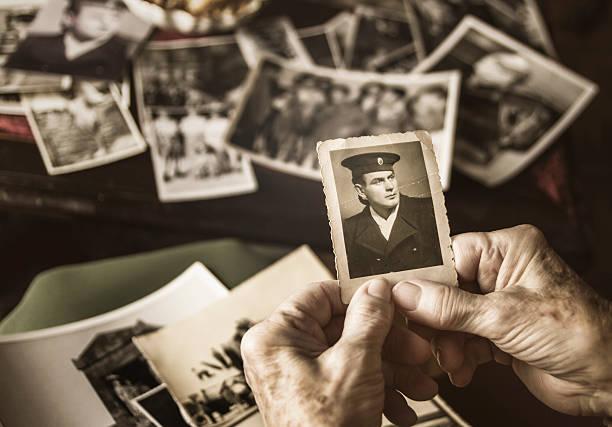 senior woman browsing dear old photographs - senior fotoboek stockfoto's en -beelden