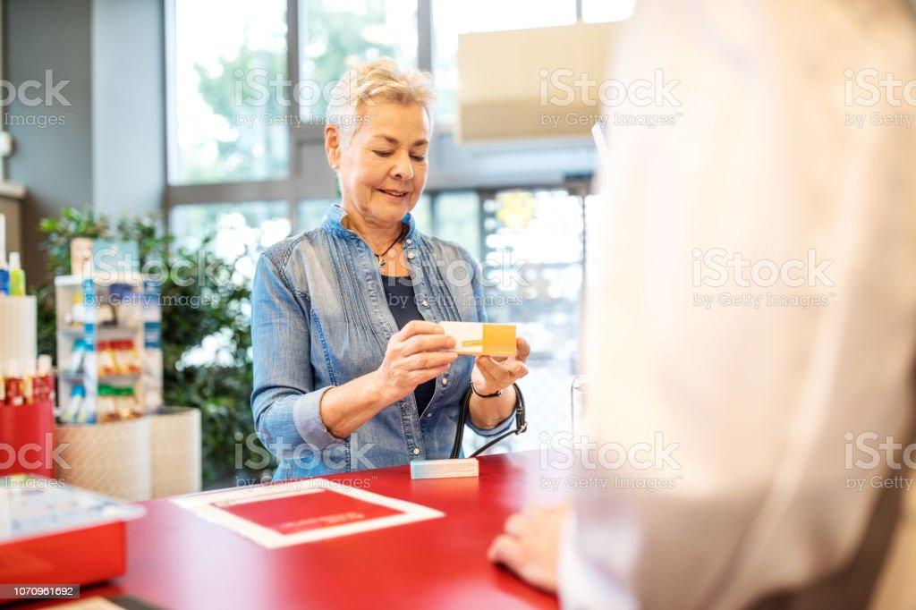 Ältere Frau Kauf von Medikamenten in Drogerie – Foto