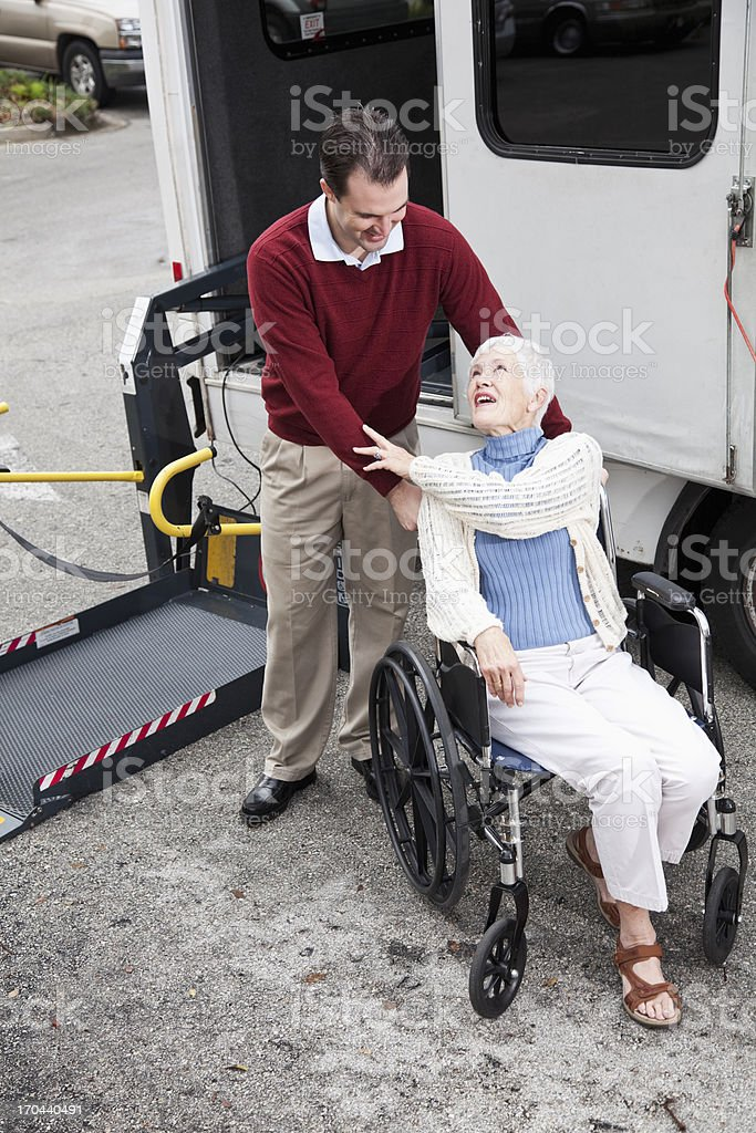Senior woman by minibus with wheelchair lift stock photo