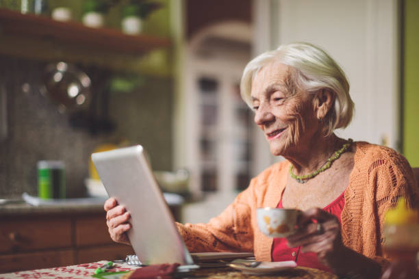 Senior woman calculating finances in her kitchen stock photo