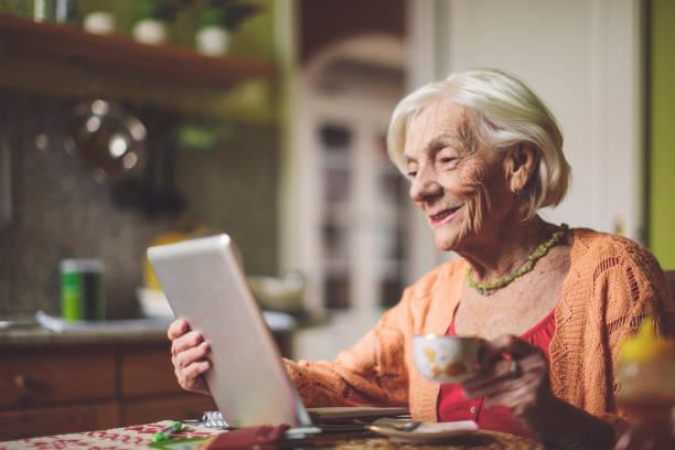 Seniorin berechnet Finanzen in ihrer Küche – Foto