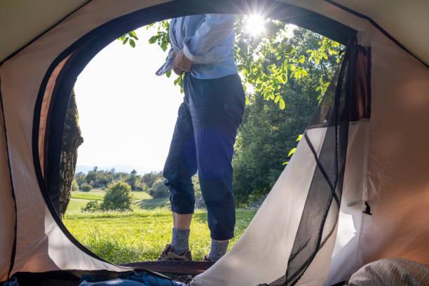 senior woman camping, morgen in-außen zeltblick - zelt stehhöhe stock-fotos und bilder