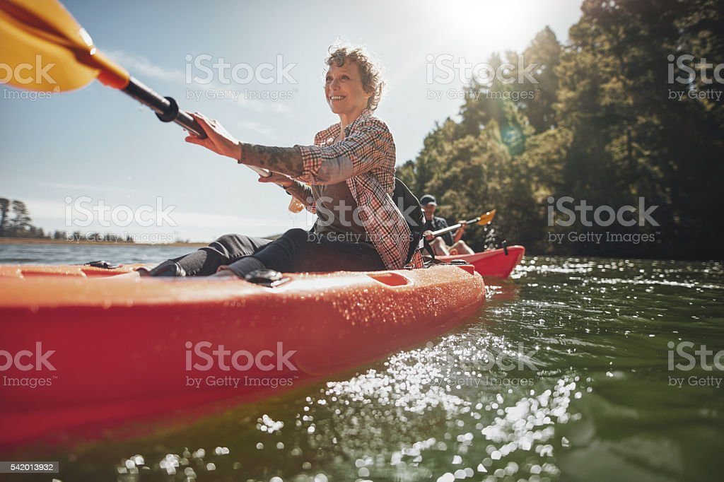 Senior woman canoeing in lake on a summer day stock photo