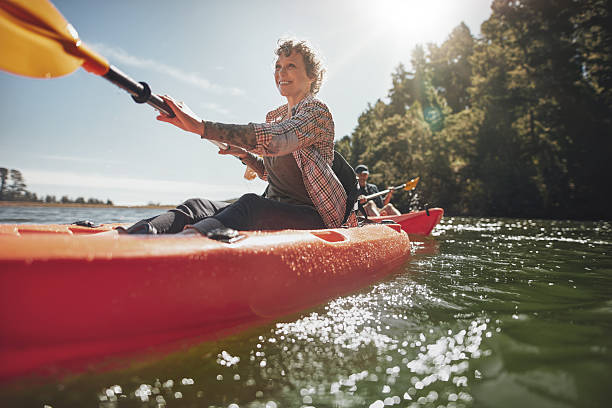 senior woman canoeing in lake on a summer day - caiaque - fotografias e filmes do acervo