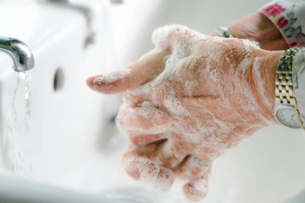 Senior woman carefully washing her hands stock photo