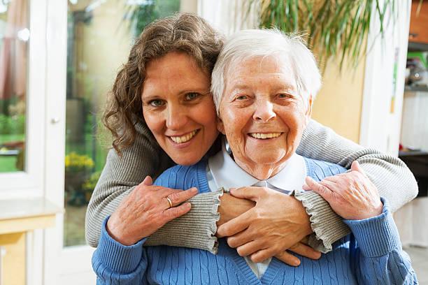 senior woman caregiver embrace stock photo