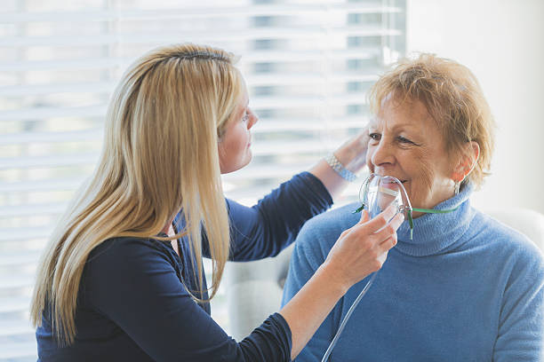Senior woman, caregiver helping with oxygen mask A senior woman in her 70s being cared for at home by her daughter or a nurse, who is helping put an oxygen mask on her face. They are sitting on chairs by a sunny window. oxygen stock pictures, royalty-free photos & images