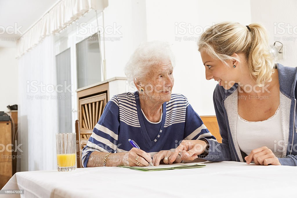 senior woman caregiver paperwork signing last will stock photo