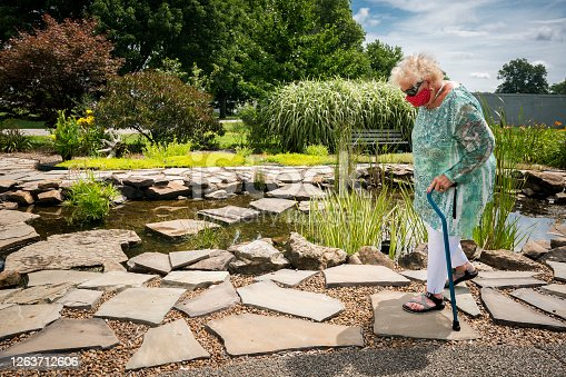 Senior woman uses a cane for balance when walking on uneven stones around a pond in a water garden, Evansville, Indiana, USA