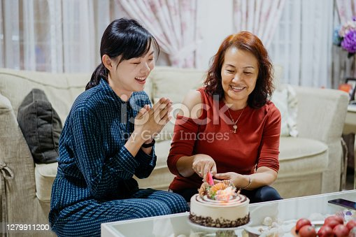 Senior woman celebrating birthday with her daughter in living room. She is slicing her birthday cake.