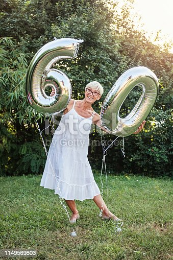 Senior woman celebrating her 60th birthday, with balloons