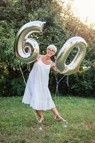 Senior woman celebrating her 60th birthday, with balloons stock photo