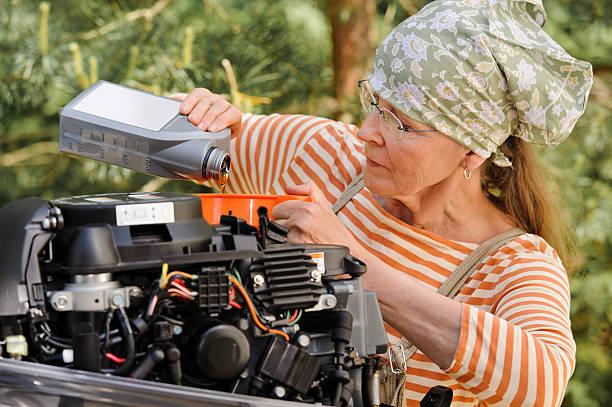 senior woman changing engine oil stock photo