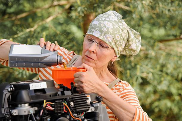 senior woman changing oil stock photo