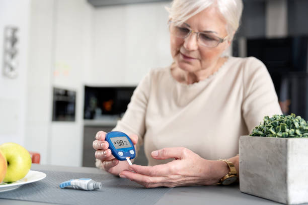 senior woman checking blood sugar level at home - diabetic stock photos and pictures