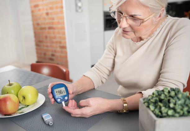 seniorin überprüft blutzuckerspiegel zu hause - hyperglycemia stock-fotos und bilder