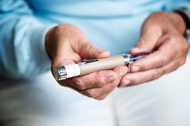 Femme Senior vérifiant son Dosage l'insuline. - Photo