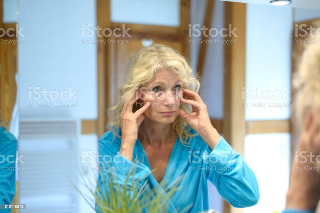 Senior woman checking her wrinkles in a mirror stock photo