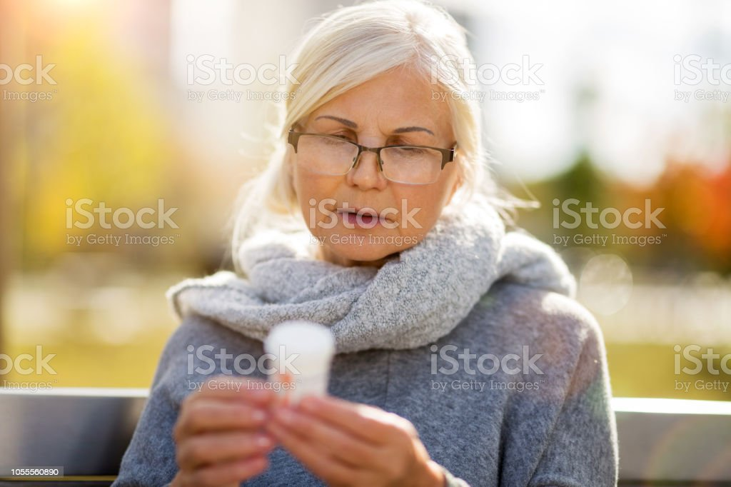 Senior woman checking label on medication stock photo