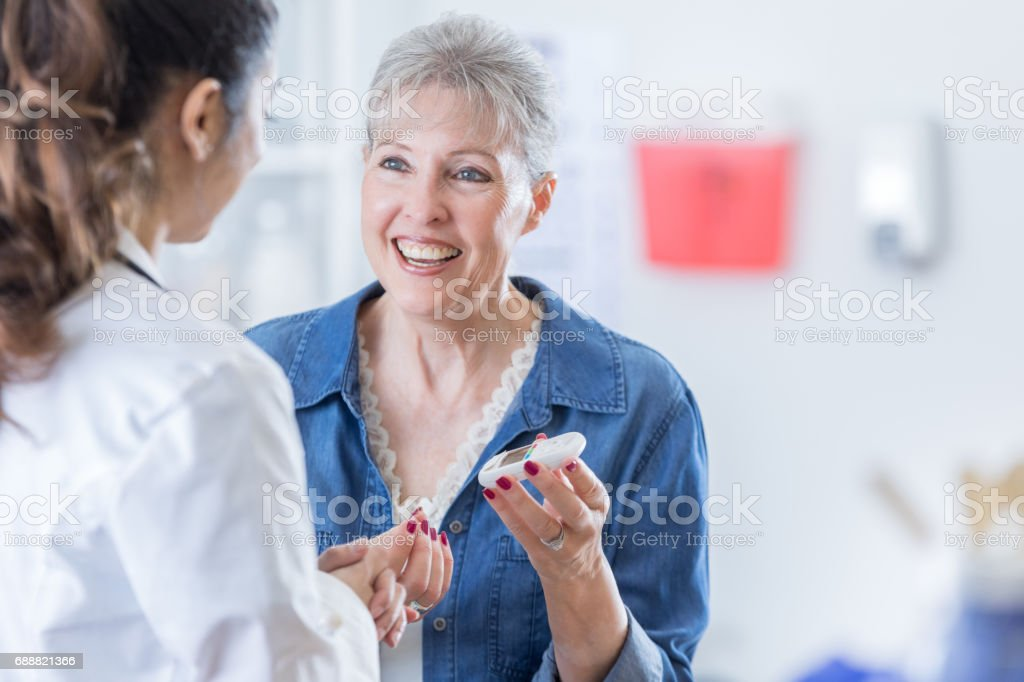 Senior woman checks blood sugar level stock photo