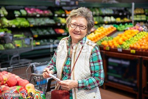Senior woman shopping for produce.
