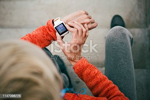 Active senior woman checks her heart rate on smart watch