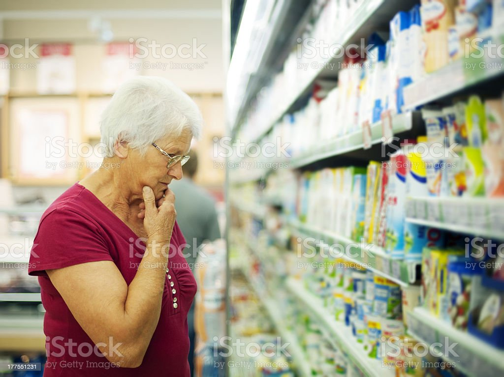 Senior woman choosing a dairy products at supermarket stock photo
