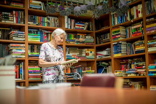 istock Senior Woman Choosing Book In The Nursing Home Library 685864326