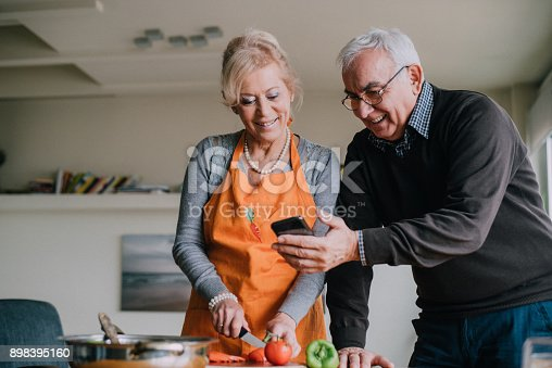 A photo of a senior woman chopping salad in the kitchen while a senior man is showing something to her on the phone.