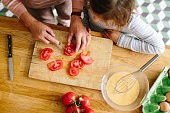 istock Senior woman chopping tomatoes with her granddaughter in kitchen 466336294