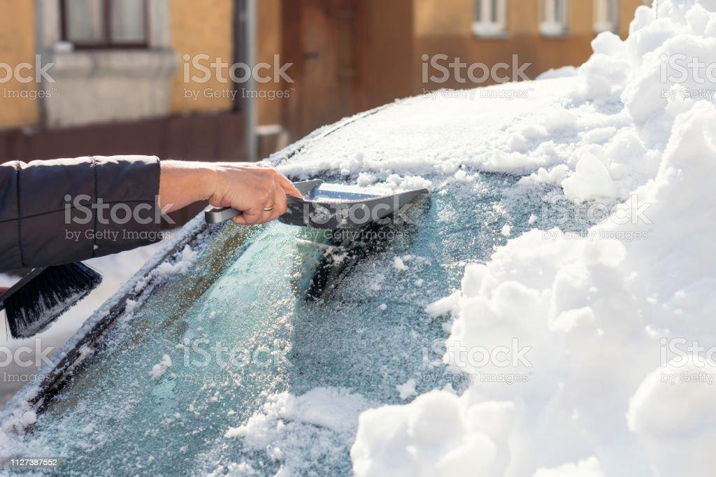 Ältere Frau, die Reinigung des Schnee von einem Auto – Foto