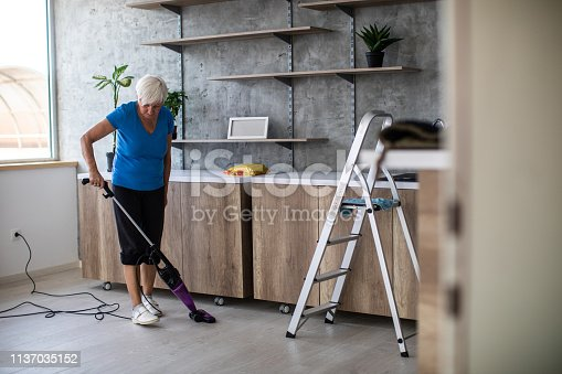 Senior woman with short, gray hair cleaning room with modern vacuum cleaner on day