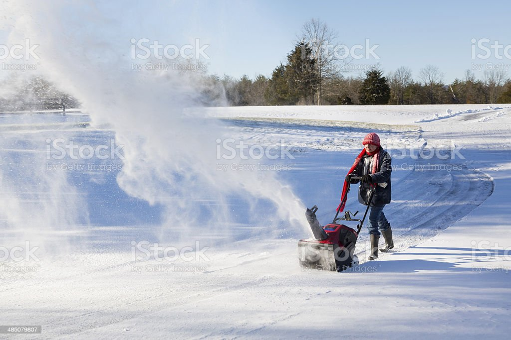 Senior woman clearing drive with snowblower stock photo